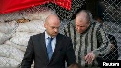 Представник ОБСЄ виводить звільненого інспектора (п) з захопленої сепаратистами міськради Слов'янська, 27 квітня 2014 року