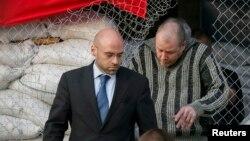Сотрудник специальной миссии ОБСЕ в Украине покидает мэрию вместе с освобожденным гражданином Швеции. Славянск, 27 апреля 2014 года.