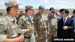 Қорғаныс министрі Әділбек Жақсыбеков (оң жақта) әскерилер арасында. Алматы облысы, 4 маусым 2012 жыл.
