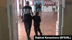 Майып баласын жетелеген эне. Кыргызстан