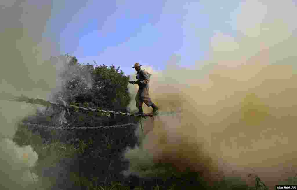 Indian Army soldiers cross a rope bridge amid smoke from canisters as they showcase their skills during a training session in Bangalore. (AP/Aijaz Rahi)