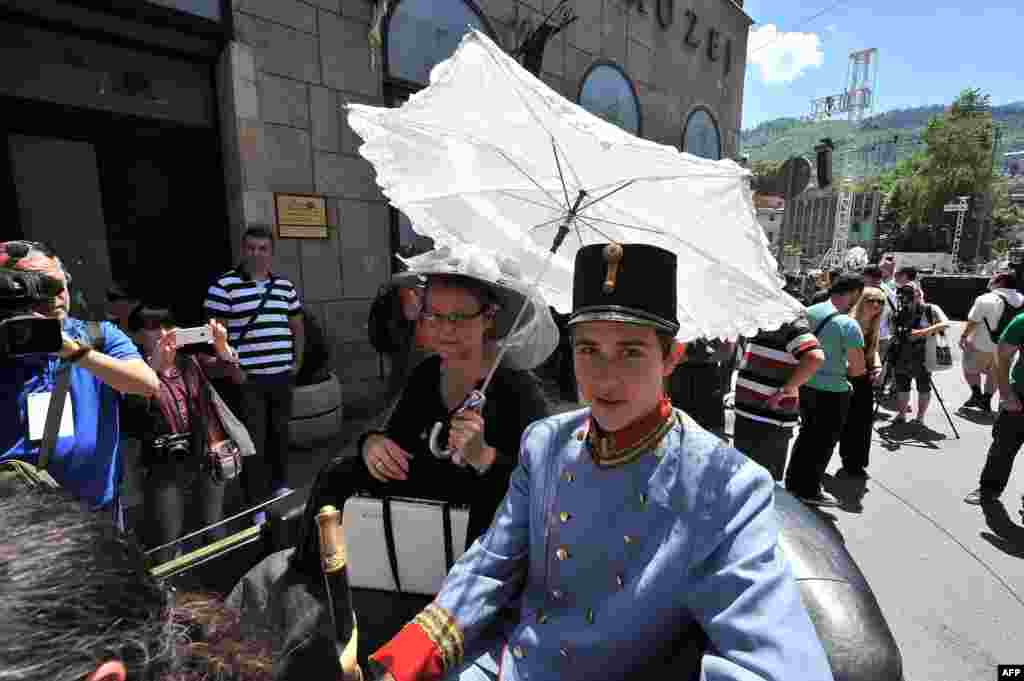 "Tourists dressed in period costumes pose for photos inside a replica of the ""Graf & Stift"" car, in front of the town museum, at the street corner in downtown Sarajevo where Gavrilo Princip assassinated Austro-Hungarian heir to the throne Archduke Franz Ferdinand in 1914. (AFP/Elvis Barukcic)"