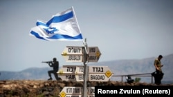 An Israeli soldier stands next to signs pointing out distances to different cities, on Mount Bental, an observation post in the Israeli-occupied Golan Heights that overlooks the Syrian side of the Quneitra crossing, May 10, 2018