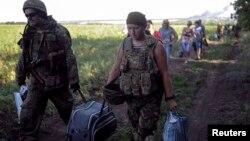 Українські військові з батальйону «Айдар» допомогають місцевим мешканцям покинути селище Металіст, 11 липня 2014 року