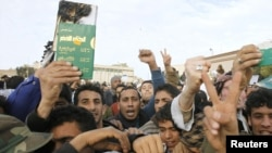 """Protesters hold up a destroyed copy of dictator Muammar Qaddafi's """"Green Book"""" as they chant antigovernment slogans in Tobruk on February 22."""
