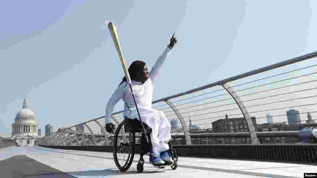 Paralympian Ade Adepitan waves to the crowd below as he carries the Olympic flame across the Millennium Bridge in front of St. Paul's Cathedral in London on July 26. (REUTERS/Luke MacGregor)