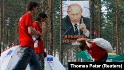 """Членови на про-Кремq младинско движење """"Наши"""" минуваат покрај постер што го покажува рускиот претседател Владимир Путин во летниот камп на езерото Селигер, на околу 300 км северо-западно од Москва на 17 јули 2007 година."""