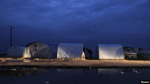 Tents housing Syrian refugees are reflected in pools of rainwater in the Bab al-Salam refugee camp in Azaz, near the Syrian-Turkish border.