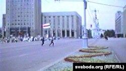 Людзі зь бел-чырвона-белым сьцягам бягуць да Дому ўраду пасьля абвяшчэньня Незалежнасьці Беларусі, 25 жніўня 1991 году