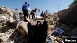 A woman reacts at the site of a suicide bomb attack on a Shi'ite mosque in Mussayab on September 30.