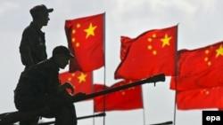 Российские солдаты сидят на БТР перед китайскими флагами после антитеррористического учения Мирная миссия ШОС.