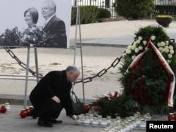 Ярослав Качиньский возлагает цветы к мемориалу памяти жертв трагедии в Варшаве. 2011 год