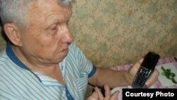 Виктор Тысяцкий держит сотовый телефон со встроенным диктофоном.