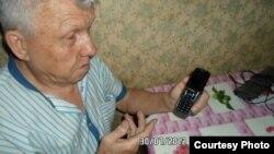 Виктор Тысяцкий қол телефон ұстап отыр.