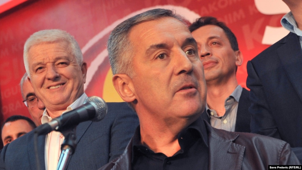 Montenegro's outgoing Prime Minister Milo Djukanovic (center), with close ally Dusko Markovic (left), who was named to succeed him