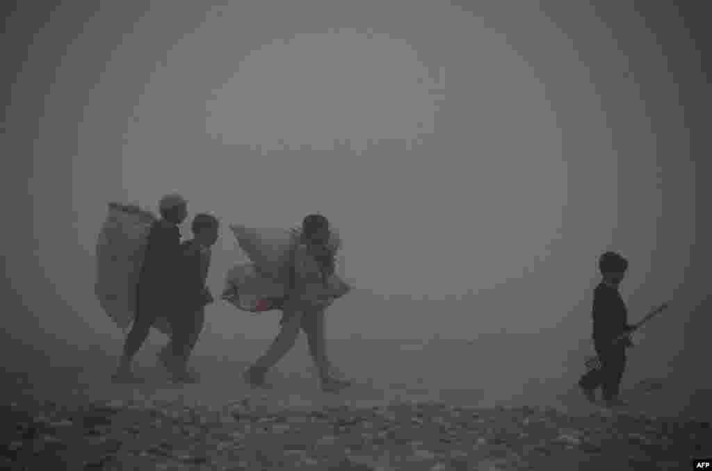 Afghan children carry bags as they walk through dense fog on the outskirts of Jalalabad. (AFP/Noorullah Shirzada)