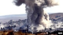 Smoke rises after an airstrike by a suspected alliance war plane on Islamic State targets in the west of Kobani on October 8.