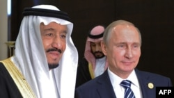 Russian President Vladimir Putin (C) poses with Saudi King Salman bin Abdulaziz Al Saud during a meeting on the sidelines of the G20 summit in Antalya, November 16, 2015