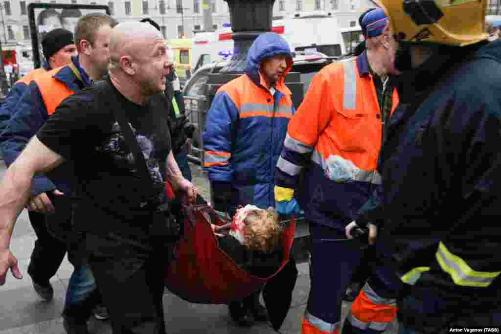 An injured person is helped by emergency services outside the Sennaya Ploshchad subway station.