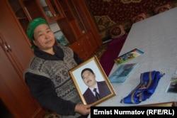 Чинара Бечелова с портретом покойного мужа. 2011 год.
