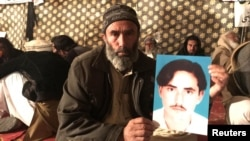 A member of Pakistan's Pashtun community holds a picture of Naqibullah Mehsud, whose extrajudicial killing by Karachi police sparked nationwide protests.