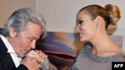 """Lola Karimova-Tillyaeva, in her role as Uzbek ambassador to UNESCO, speaks with French actor Alain Delon before attending a 2009 gala dinner for the launch of the charity fund """"Uzbekistan 2020"""" in Paris."""