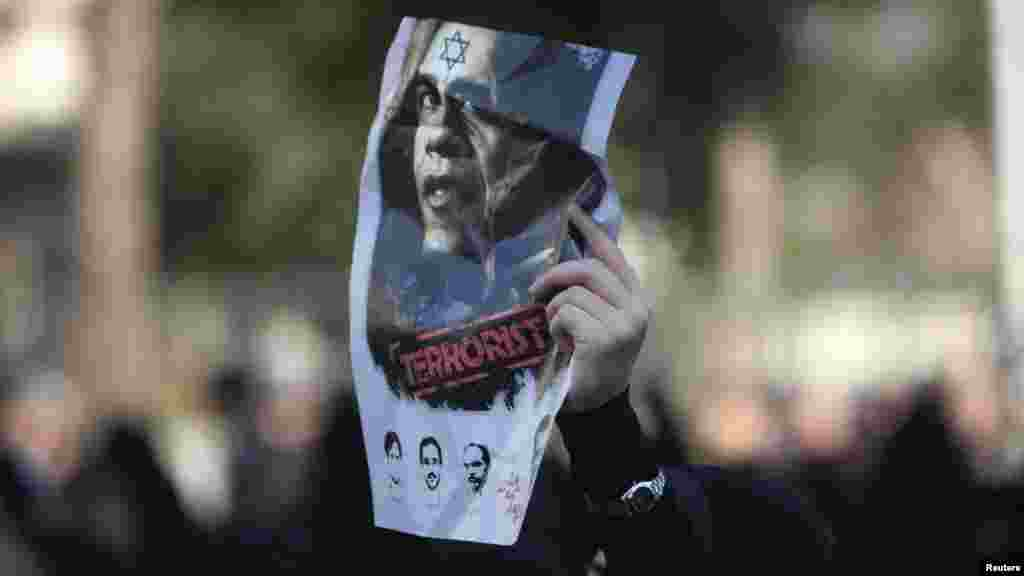 A worshipper holds an anti-U.S. poster during the funeral for nuclear scientist Mostafa Ahmadi Roshan, who was killed in a bomb blast in Tehran. (Photo by Morteza Nikoubazl for Reuters)