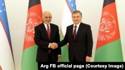 Uzbekistan's President Shavkat Mirziyoev (R) shaking hands with the Afghan President Ashraf Ghani in Tashkent on March 27.