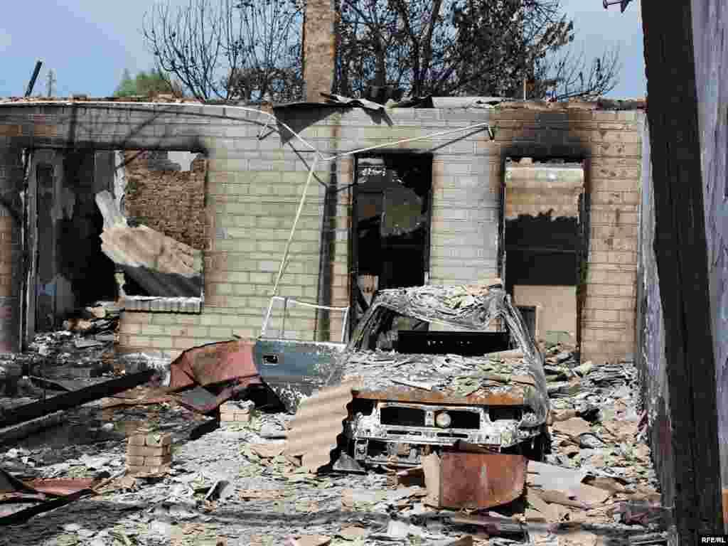 Burned-out buildings and a vehicle in the ethnic Uzbek Cheremushky neighborhood of Osh -