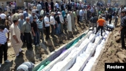 People gather at a mass burial for the victims of a purported artillery barrage from Syrian forces in Houla.
