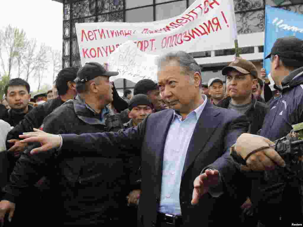 Телохранители помогают Бакиеву покинуть митинг своих сторонников после нападения сторонников Временного правительства. Ош, 15 апреля 2010 года.
