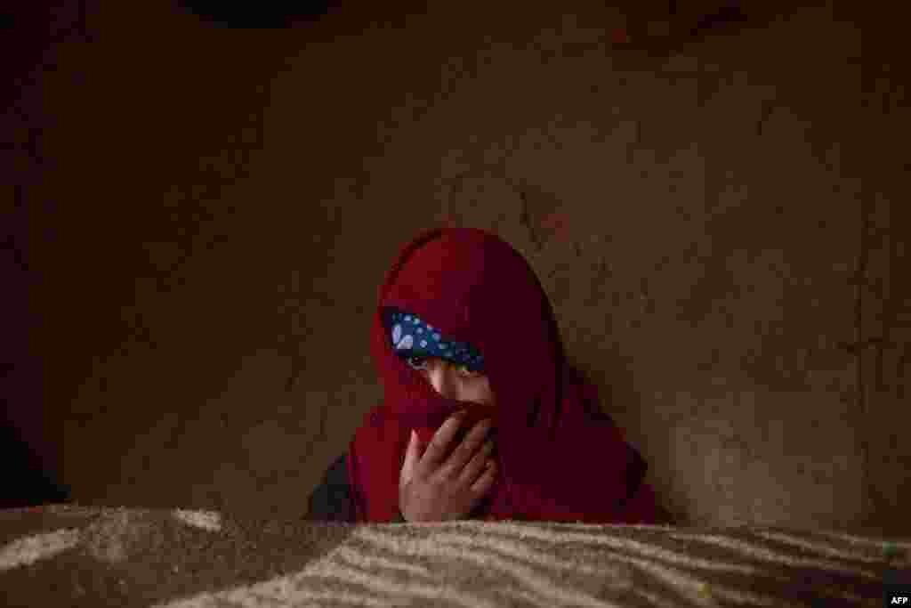An internally displaced Afghan child warms herself near a wood-burning stove as winter continues on the outskirts of Herat. (AFP/Aref Karimi)