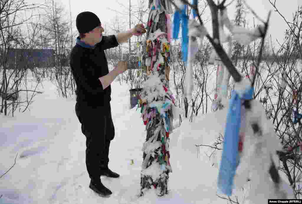 In the Yakutia region of Siberia, many ethnic Russians -- despite being Orthodox Christians -- show deep respect for the rituals of the shamanic world. This truck driver is leaving a gift of cigarettes at a sacred site, a ritual he carries out each time he makes the treacherous journey along the frozen Indigirka River.