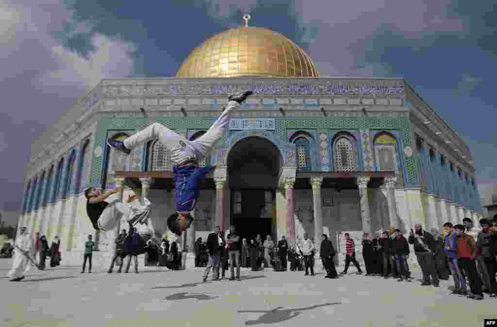 Palestinian youths practice parkour outside the Dome of the Rock mosque at the Al-Aqsa mosque compound following Friday Prayers in the Old City of Jerusalem. (AFP/Ahmad Gharabli)