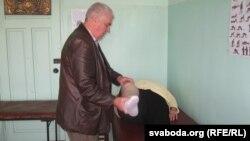 Лекар Іван Шэга аглядае спадарыню, якая прыйшла да яго па кансультацыю