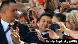 Volodymyr Zelenskiy takes selfies with supporters prior to his inauguration.