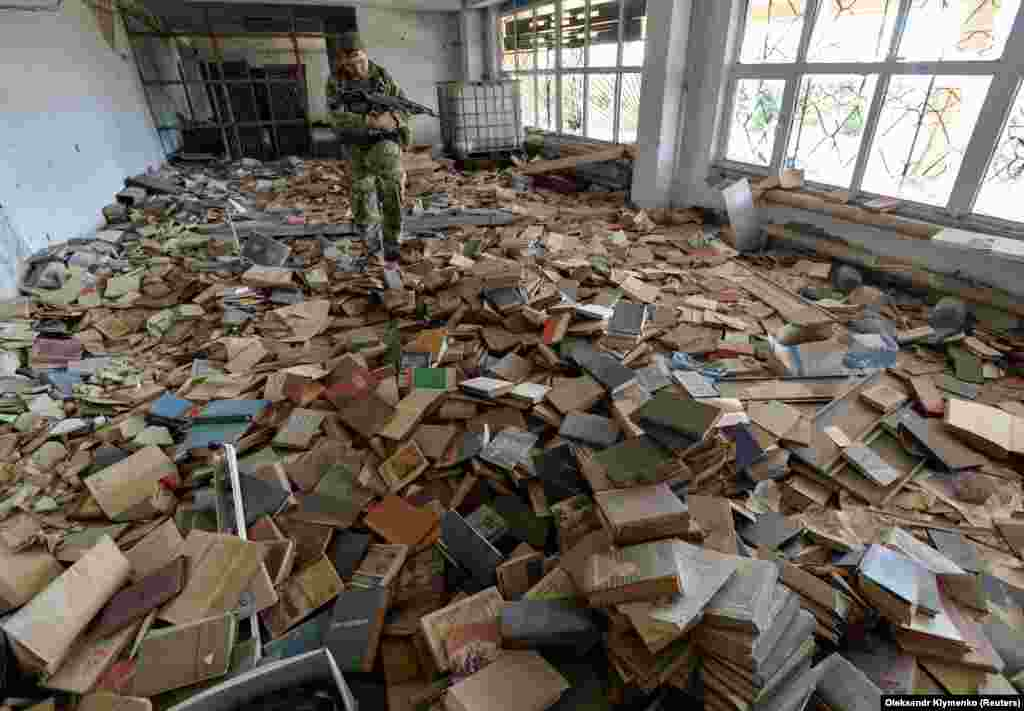 A Ukrainian serviceman inspects an abandoned library near his position on the front line in the town of Maryinka. (Reuters/Oleksandr Klymenko)