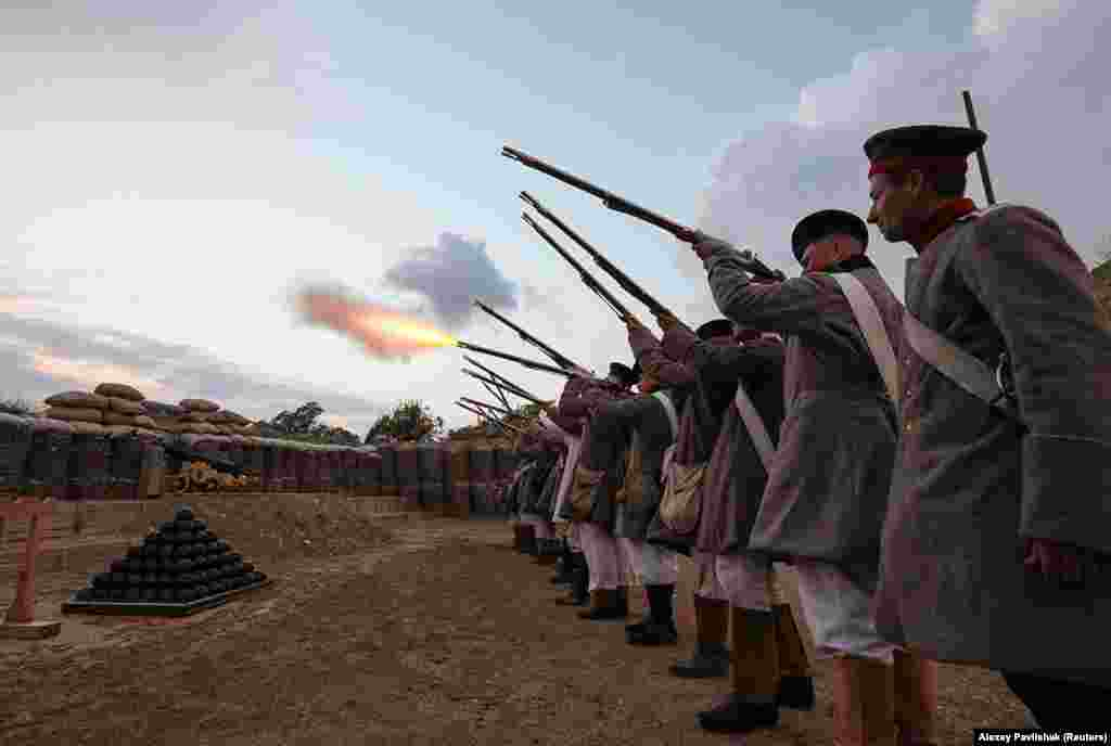 """A line of """"Russian soldiers"""" fires a volley during a re-creation of a battle from the 1853-56 Crimean War."""