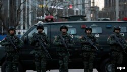 Вооруженные полицейские охраняют торговый центр в районе Санлитун в Пекине, 24 декабря 2015 года