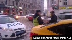 Кыргызстандык айдоочуну МАИ кызматкери текшерүүдө. Москва, январь