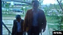 Бұрынғы бас дәрігер Ж. Күшалиев (екінші) қорғаушысы М.Төлегеновпен бірге сотқа келе жатыр. Атырау, 13 мамыр, 2009 жыл.