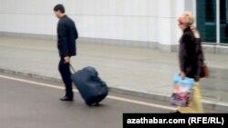 Aşgabadyň aeroportyndan gaýdyp barýan türkmenistanlylar.