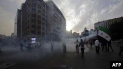 Ливанцы, несмотря на клубы слезоточивого газа, пытаются штурмовать здание правительства. Бейрут, 21 октября 2012 года.
