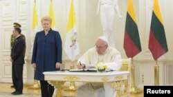 Pope Francis signs a guest book next to Lithuanian President Dalia Grybauskaite on September 22.