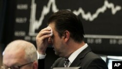 Germany -- Market analyst Robert Halver wipes his face at the German stock exchange in Frankfurt, 05Aug2011
