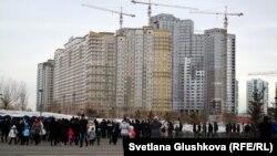 Люди проходят мимо строящегося жилого дома в Астане. 22 марта 2013 года.