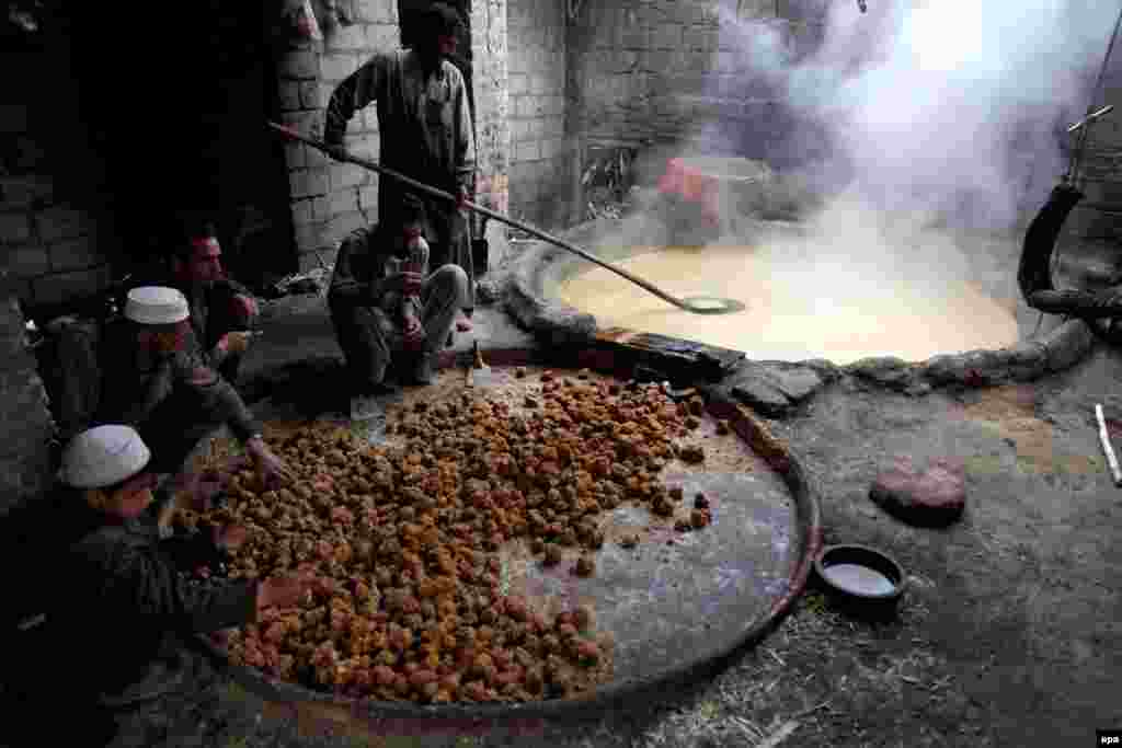 Pakistani men prepare brown sugar from sugarcane juice. (AFP/Bilawal Arbab)