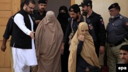 Pakistani security officials escort Afghan refugee Sharbat Gula (center, in burqa) after a court hearing in Peshawar on November 4.