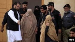 Pakistani security officials escort Sharbat Gula (center, in burqa), after a court hearing in Peshawar on November 4.