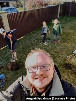 Андрэй Курэйчык і ягоныя дзеці працуюць у саду.